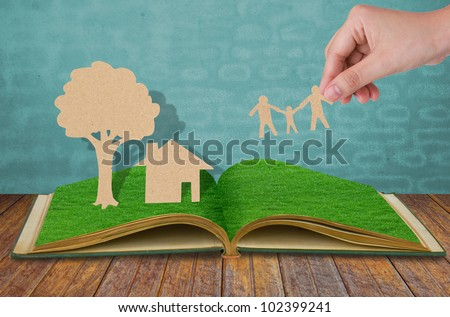 Paper cut of family symbol  on old grass book