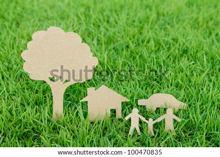 Paper cut of family with house , tree and car on fresh spring green grass