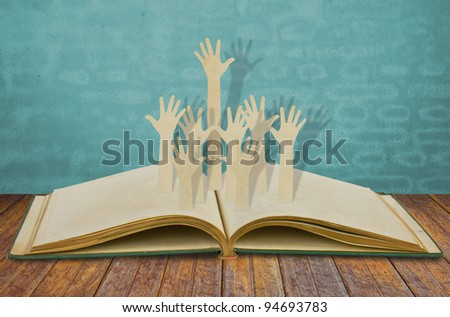 Paper cut of Hands volunteering or voting on old book