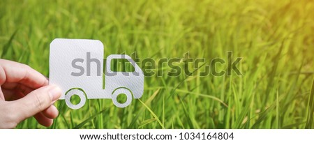 Paper cut of truck on green grass background, earth day concept with copy space, spring time, background silhouette delivery e-commerce transport save energy concept panoramic banner