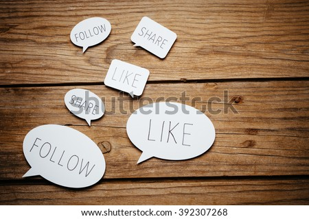 Paper cut speech bubbles with social media concepts on wooden background. #392307268