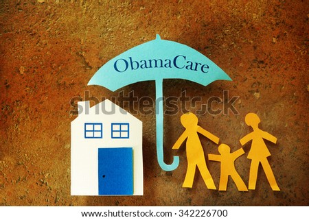 Paper cutout family with house under an Obama Care umbrella