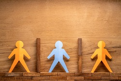 Paper cutout human figures separate by wooden blocks on wood background, social distancing during COVID-19 virus outbreak concept with room for copy space