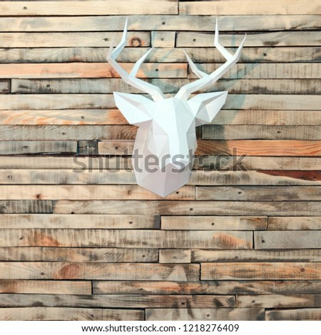 Paper deer head on the wall of wooden bars. Designer background for decoration in the room. New Year's wall decoration. Square picture.