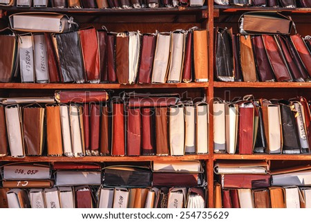 Paper documents stacked in archive on shelf