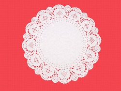 Paper doily on textured red. Celebration background.
