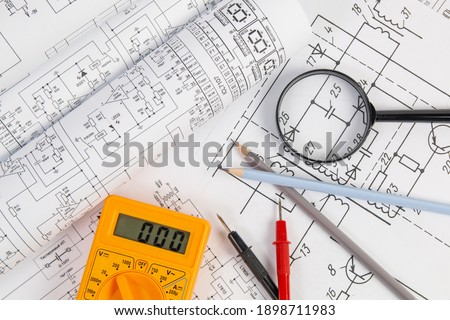 paper electrical engineering drawings, pencil, magnifying glass and digital multimeter Stock photo ©