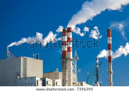 Paper factory with main chimneys expelling smoke into a deep blue sky - horizontal orientation