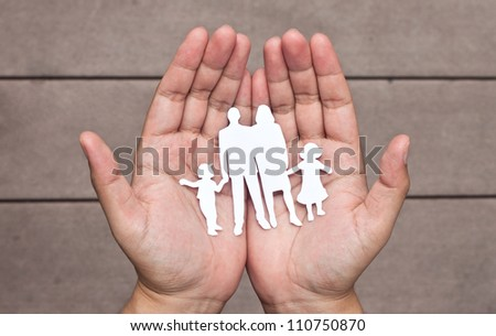 Paper family in hands on brown wood background