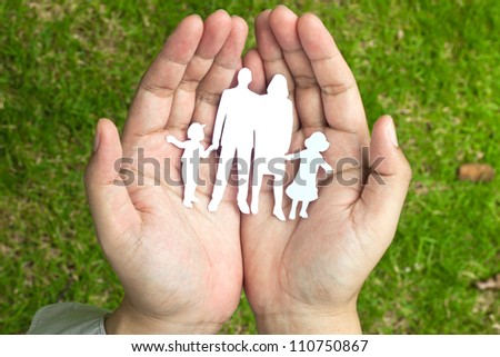 Paper family in hands on green grass background