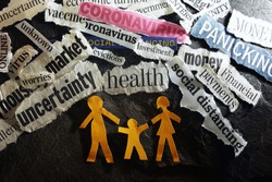Paper family of three surrounded by Corona Virus and economic news headlines