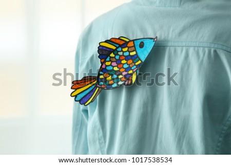 Paper fish on man's back, closeup. April fool's day prank Photo stock ©
