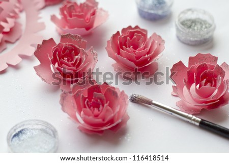 Paper flowers for creativity. Placing glitter on the pink paper flowers