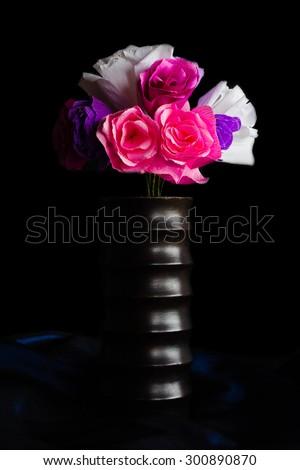 paper flowers in wooden vase ( focus on vase) on black background