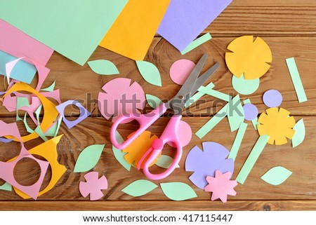 Paper flowers, paper sheets, scissors, paper scrap on a wooden table. Paper flower craft for kids. Children\'s art project.