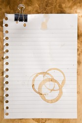 Paper from a notepad with coffee stains and clip
