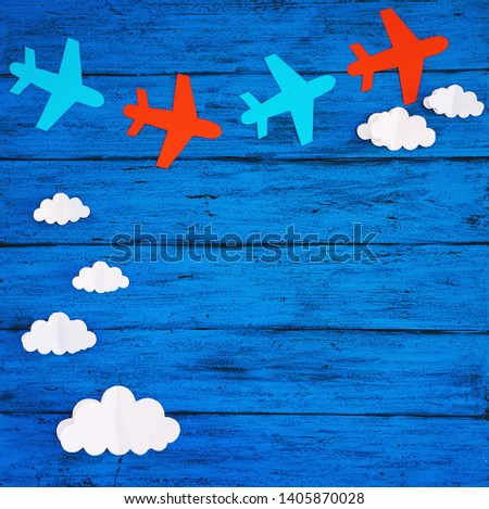 Paper handmade crafts: clouds and airplanes on the blue wood background. Top view, copy space. #1405870028