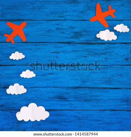 Paper handmade crafts: clouds and airplanes on the blue wood background. Top view, copy space. #1414587944