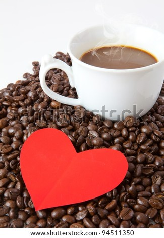 paper heart and cup on coffee beans