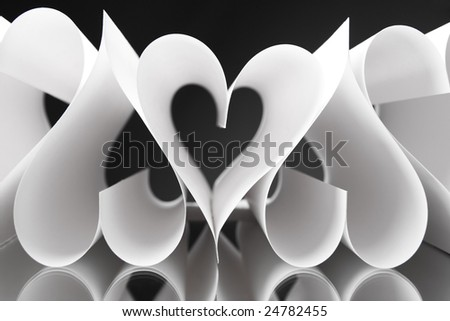 Paper heart shapes next to each other over black background
