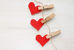 Paper heart wall garland - DIY valentines decor idea, pinned on twine, white wooden background