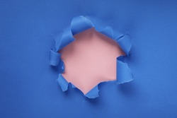 Paper hole with torn sides on a blue-pink background. Through the paper. A ragged hole.An accurate shot. The concept of advertising and breakthrough. Design for text, print, or advertising content.