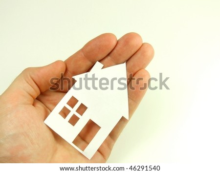 Paper house on human hand concept