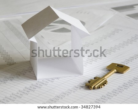 Paper house with key on financial documents. Series. Shallow DOF.