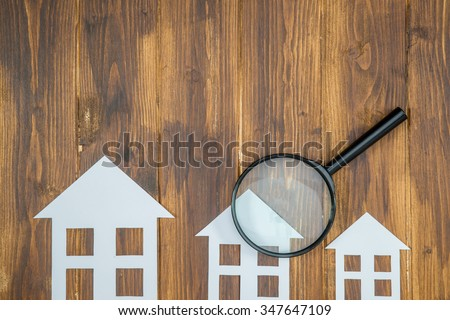 paper house with Magnifying Glass, House hunting on wooden background