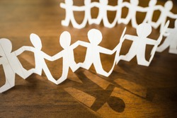 Paper human chain on wood background, focus at the one of team that has a light and own shadow, different person, new member, leadership or someone in a role of team