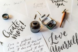 Paper, ink, calligraphy pens and inscriptions. Lettering workshop details. Inscribing ornamental decorated letters. Calligraphy, graphic design, lettering, handwriting, creation concept