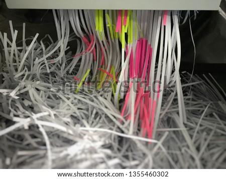 Paper into shredder machine. Document shredder with paper shred in black bag. Destroying sheet of paper.  Foto stock ©