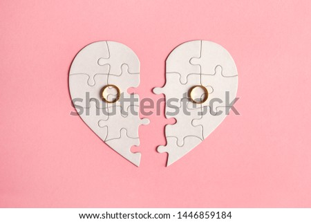 paper jigsaw puzzle heart split in two pieces with golden wedding rings, top view, flat lay, divorce and breakup concept #1446859184