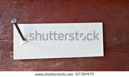 Paper label attached on wood wall with nail.