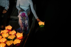 Paper lantern in Vietnamese woman hand in Hoi An ancient town, Vietnam.  The lanterns are set into the river as an offering and to worship their ancestors as well as the God of the land
