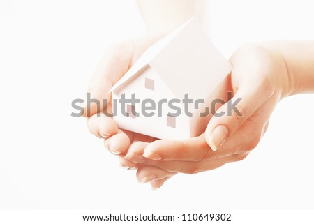 Paper miniature of house on female hands