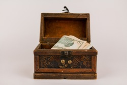paper money dollars in a wooden chest