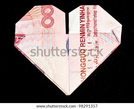 paper money folded into the heart-shaped  isolated on a black background