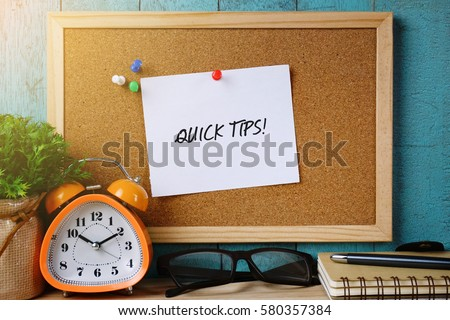 Paper note on cork board written with QUICK TIPS inscription. Plant, alarm clock, eye glasses, pen and notebook on wooden desk. Business and education concept.