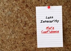 Paper note pinned on board with copy space, written self affirmation LESS INSECURITY, MORE CONFIDENCE concept of stop being insecure ,build up self-esteem by change mindset ,overcome negative thoughts