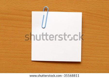Paper note with a blue clip over the wooden table