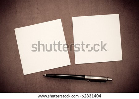 Paper note with pen on wooden background