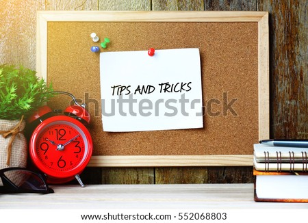 Paper note written with TIPS AND TRICKS inscription on cork board. Eye glasses, alarm clock, plant and books on wooden desk.