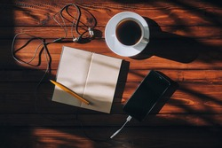 Paper notebook and black smartphone, pen, headphone and white cup of coffee lies on a brown wooden background mahogany. Copy space and mockup. Music and writter concept.