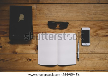 Paper notebook, black old book, sunglasses, pen and a touchscreen smartphone on the old wooden table background