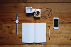 Paper notebook,watches,lomography film camera, pen and a touchscreen smartphone on the old wooden table background