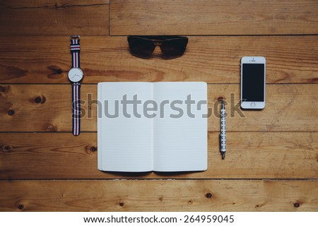 Paper notebook,watches, sunglasses, pen and a touchscreen smartphone on the old wooden table background #264959045