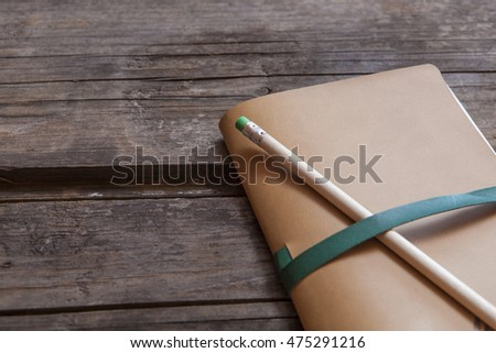 Paper notebook with leather cover with green rubber tip pencil on wooden old surface, dear diary concept or protect your idea or secrets