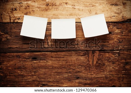 Paper notes attach to old wooden background - stock photo