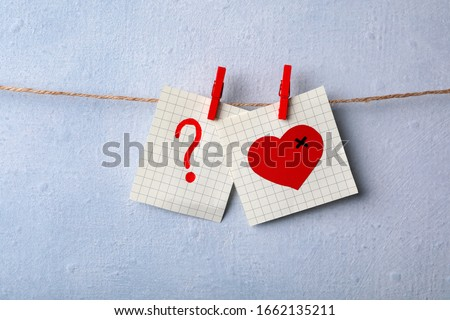 Paper notes with drawings of heart and question mark pinned on laundry string near light wall. Relationship problems concept ストックフォト ©